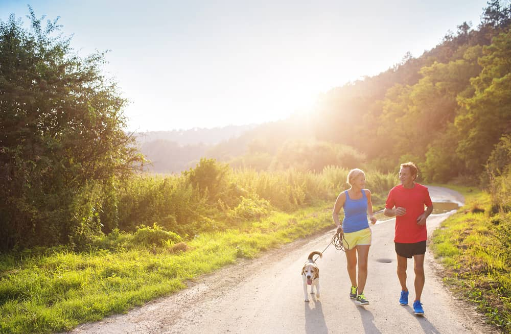 Couple and dog jogging on country road
