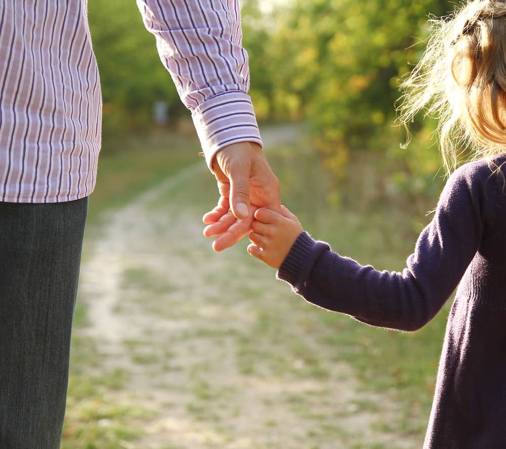 Little girl holds father's hand