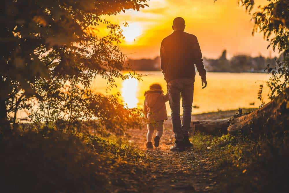 Father walks with child towards a lake